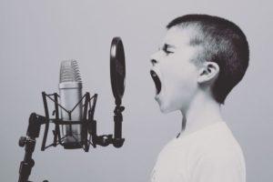 Junge schreit ins Mikrofon im Tonstudio